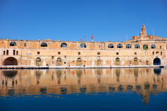 The old dock building at Bormla (Cospicua) waterfront. Malta. The old dock buildings at Bormla (Cospicua) waterfront with the Fort St. Michael Clock Tower on Stock Image