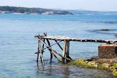Old dock and sea. Old wooden dock by the ocean Royalty Free Stock Photo