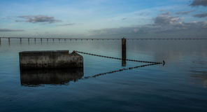Calm Water. Old dock in Tagus River with Vasco da Gama bridge in background Royalty Free Stock Photos