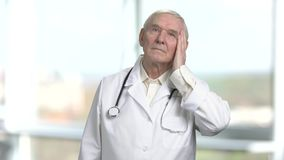 Old doctor get rid of excessive sweating. Portrait of frowning senior doctor with stethoscope. Bright windows background stock footage