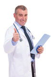 Old doctor giving you the good news. By making the ok thumbs up gesture on white background Stock Photos