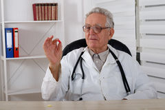 Old doctor with glasses observe red  pill Royalty Free Stock Photography