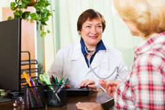 Old doctor having positive news for a patient Royalty Free Stock Photography