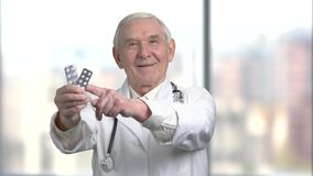 Old doctor hold the medicine strip. Male senior doctor holding in his hand a package of pills and show thumb up, blurred background stock footage
