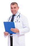 Old doctor holding a notepad is smiling to the camera Stock Photo