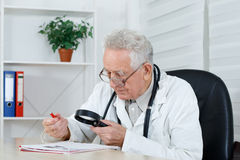 Old doctor with loupe study a literature stock photo