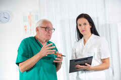 Old doctor and a nurse are consulted Royalty Free Stock Photos