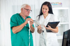 Old doctor and a nurse are consulted Royalty Free Stock Photo