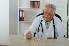 Old doctor observe colorfully pills in  consulting room. Old doctor observe lot of  pills in  consulting room Stock Photo