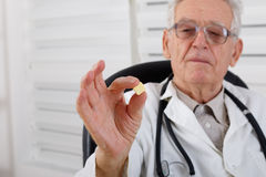 Old doctor observe yellow pill Stock Photos