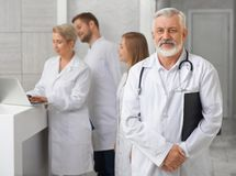 Old doctor posing, medical staff standing behind. stock images