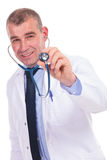 Old doctor smiling with his stethoscope in his ears Stock Images