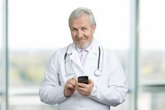 Old doctor standing, holding and typing on mobile phone.
