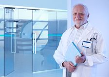Old doctor standing in MRI room of hospital. Old doctor standing in front of MRI room at hospital, holding tablet, smiling stock photos
