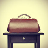 Old doctors bag on a table, with a retro filter effect Stock Photography