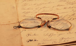 Old Document. Vintage pince-nez lying on an old handwritten document stock images