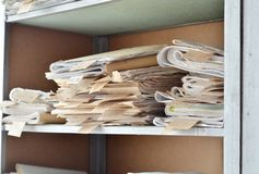 Old documents, drawings with numbers stacked on shelves in the o. Old documents, drawings with numbers stacked on shelves in office stock images