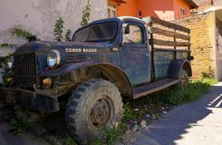 Old Dodge Power Wagon pick-up truck outside of a garage in an overgrown yard in Peru. Huaraz, Ancash / Peru: 29.  May, 2016 - old Dodge Power Wagon pick-up truck royalty free stock photo