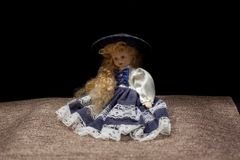 Old doll - Curly girl with shadowed face. Old doll - Curly girl on a black background with shadowed face royalty free stock image