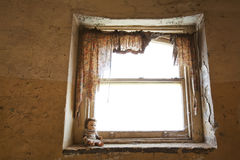 Old Doll sitting on Decrepit Window Sill Royalty Free Stock Images