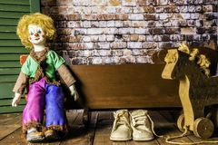 Clown Doll Rocking Baby in Cradle. Old doll sitting on red rocking chair next to antique wooden cradle worn baby shoes and wood toy horse on wood floor with stock photo