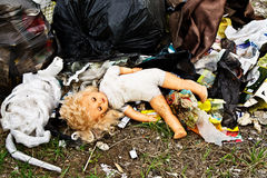 Old doll that was thrown in the trash. Recycling raw materials. Stock Photography