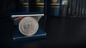 Old 1 dollar silver coin on a black table with binders and books in the background. Numismatic scene royalty free stock photography