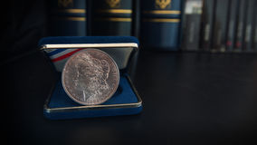 Old 1 dollar silver coin on a black table with binders and books in the background. Numismatic scene royalty free stock photos