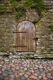 Old door. A photo of an old brown timber door in the wall. The road in front of the door is made of cobbles Royalty Free Stock Photos