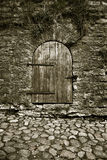 Old door. A photo of an old timber door in the wall. The road in front of the door is made of cobbles Royalty Free Stock Photos