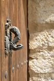 Old door with an animalistic wrought handle. The ancient wooden door is photographed against the blurred stone wall royalty free stock photo