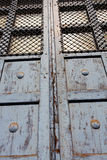 Old door with bars in the sunlight Stock Photos
