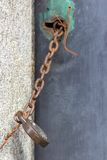 Old door chained shut with vintage padlock. An old door with paint peeling is chained shut with an old-fashioned padlock. The chain is rusted and attached to the Stock Photos