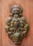 Old door clapper with lions. Very old door clapper with emblem between two lions, monstrous face and rust on a wooden door royalty free stock image