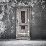 Old door in dark concrete wall with exclamation sign Stock Image