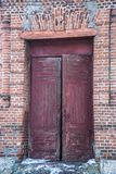 Old door entrance to the building. Red gate, brick building Royalty Free Stock Image