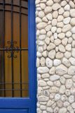 Old door with facade made with sea rounded stones Stock Photography