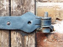 Old door fitting. An old door hardware at one of a weathered wooden door Stock Images