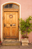 Old door with flowers and tree stock photography