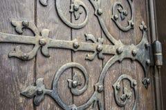 Close up of big ornate cast iron door hinge on wood plank door royalty free stock image