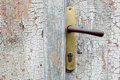 Old door with handle. Old door with cracked paint and a handle Stock Photo