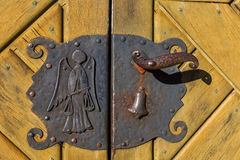 Old door handle with angel, bell and weigher Stock Photography