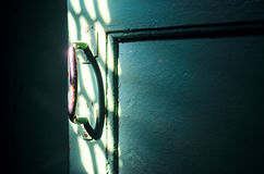 The old door handle in the dark room. Is lit by the rays of sunlight. Forward to light concept Stock Photos