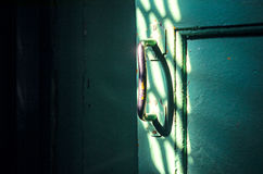The old door handle in the dark room. Is lit by the rays of sunlight. Forward to light concept Royalty Free Stock Photo