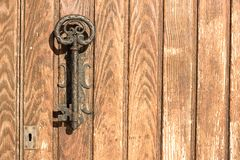 The old door handle in the form of key. Royalty Free Stock Photo