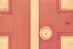 Old door handle on red wall in vintage tone Royalty Free Stock Photo