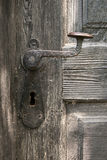 Old door handle on wooden door Stock Photo