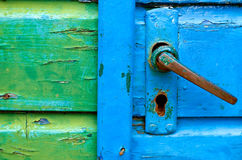 Old door handles. With blue and green painted door detail Stock Photo