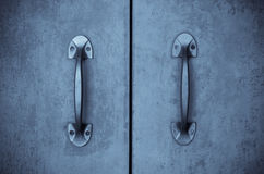 Old door handles. With an old double door painted with blue Royalty Free Stock Image