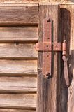 Old door hinge. On wooden door stock image